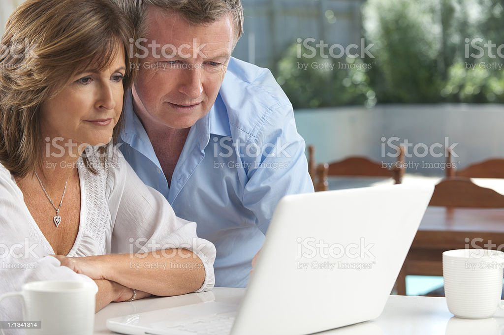 Worried mature couple using wireless technology royalty-free stock photo