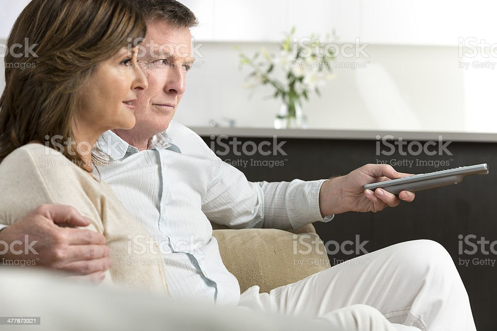 Worried mature couple watching TV royalty-free stock photo
