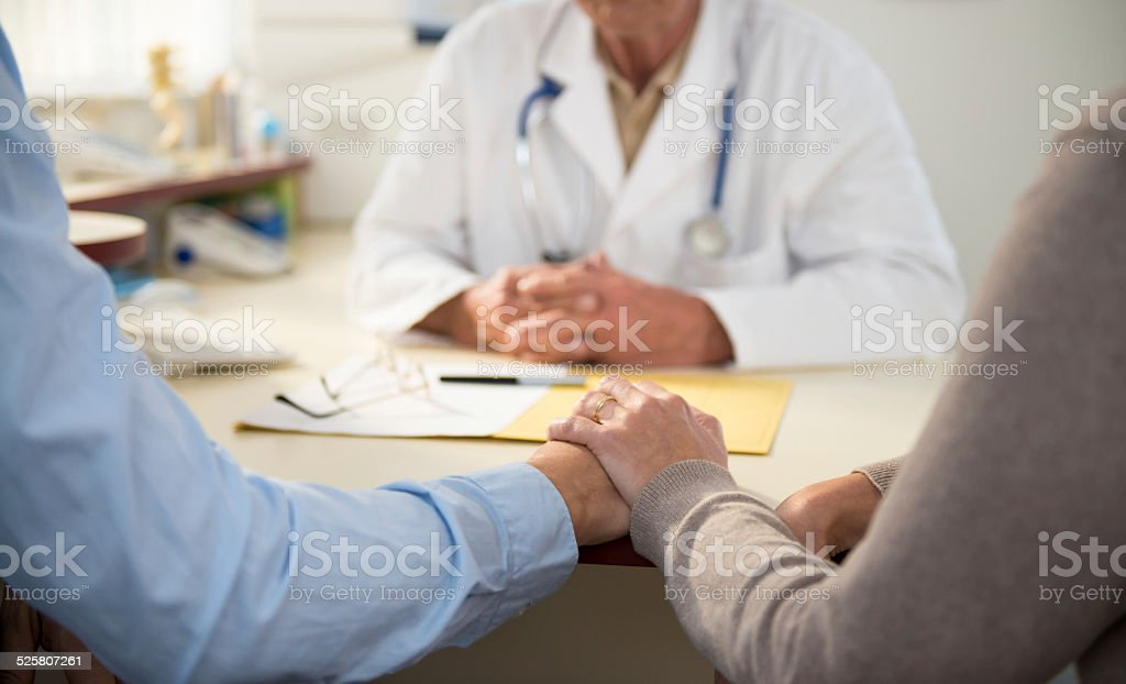 Worried mature couple with doctor stock photo