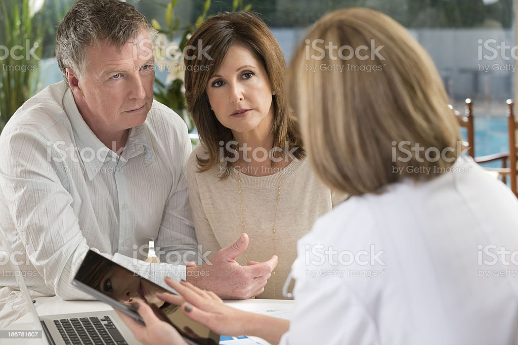 Worried mature couple with doctor using digital tablet. royalty-free stock photo