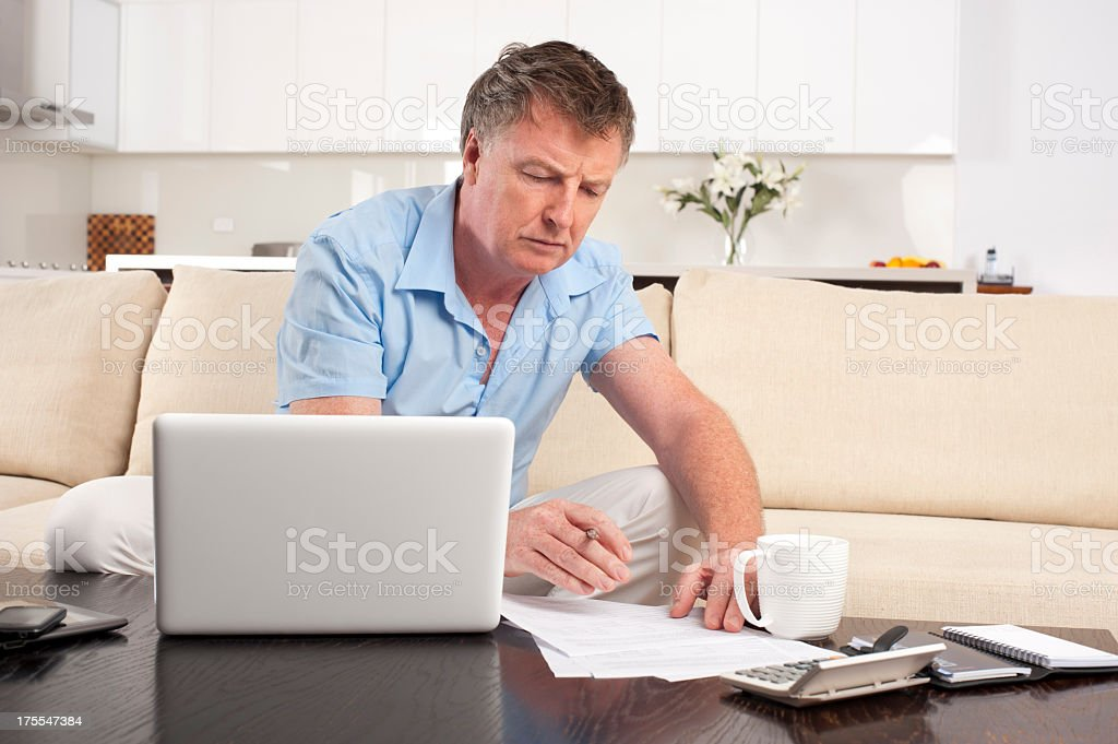 Worried Mature man doing paperwork with laptop stock photo