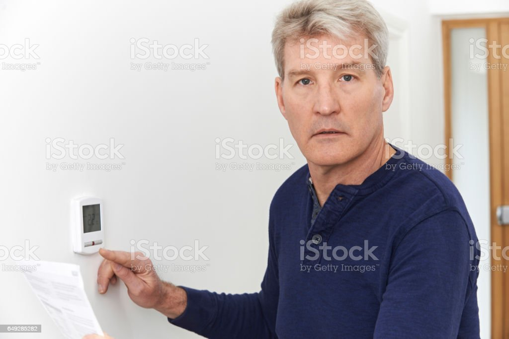Worried Mature Man With Bill Turning Down Central Heating Thermostat stock photo