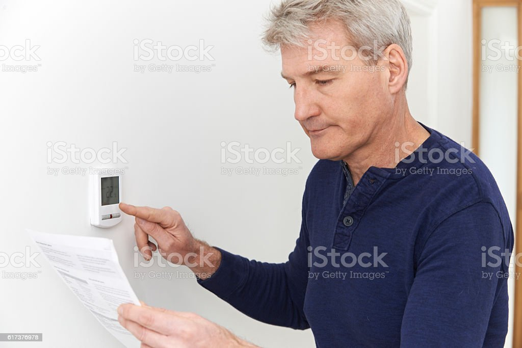 Worried Mature Man With Bill Turning Down Heating Thermostat stock photo