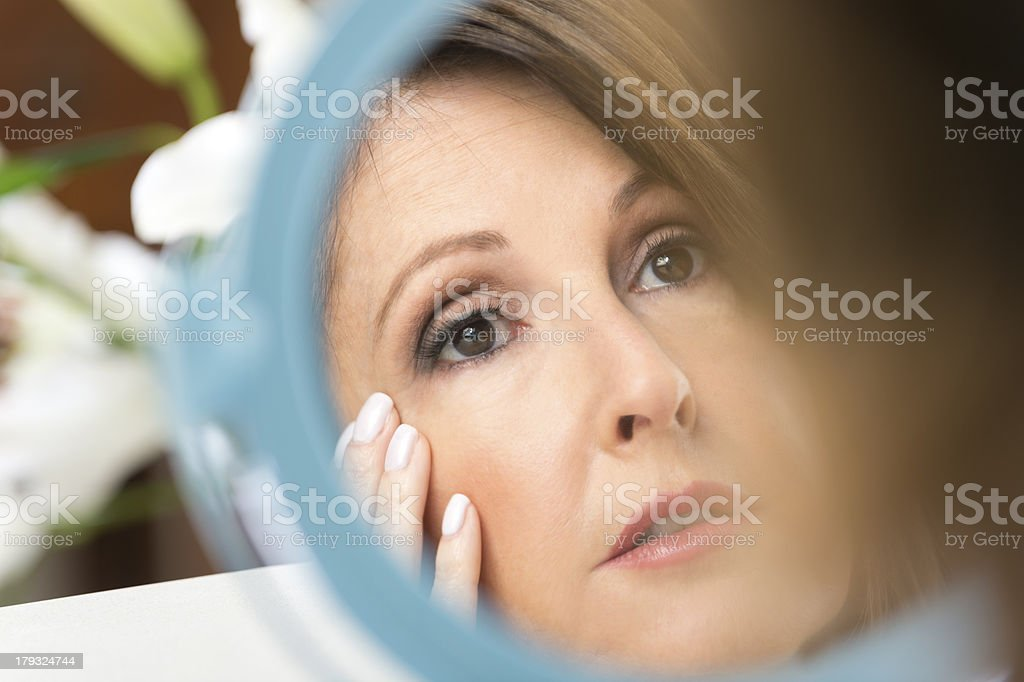 Worried mature woman looking in the mirror. royalty-free stock photo