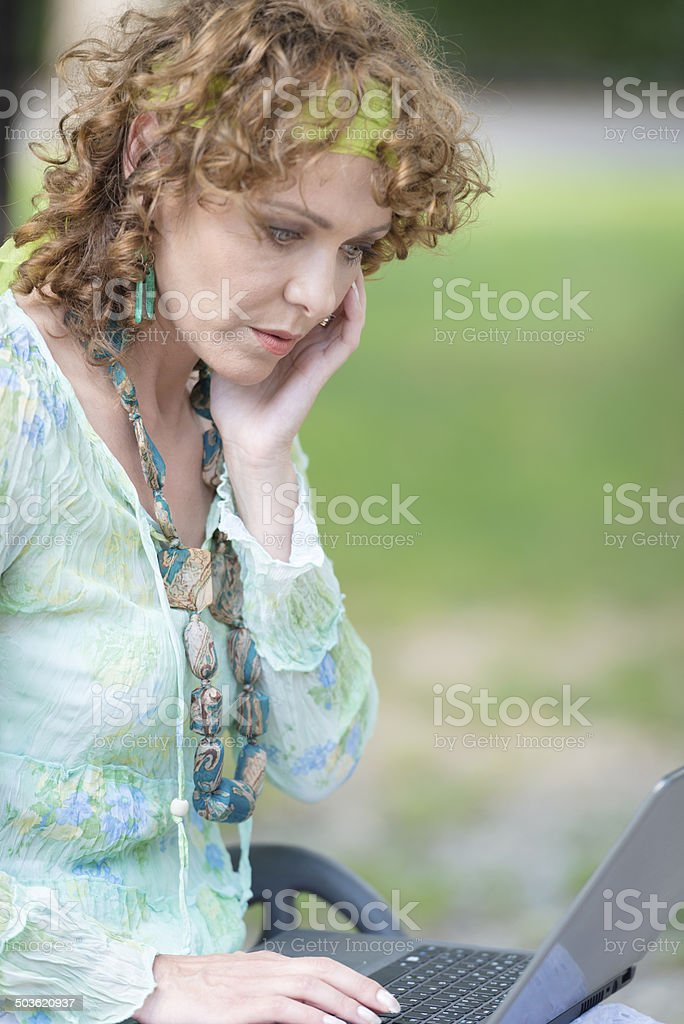Worried mature Woman with Laptop, City Park, Italy, Europe stock photo