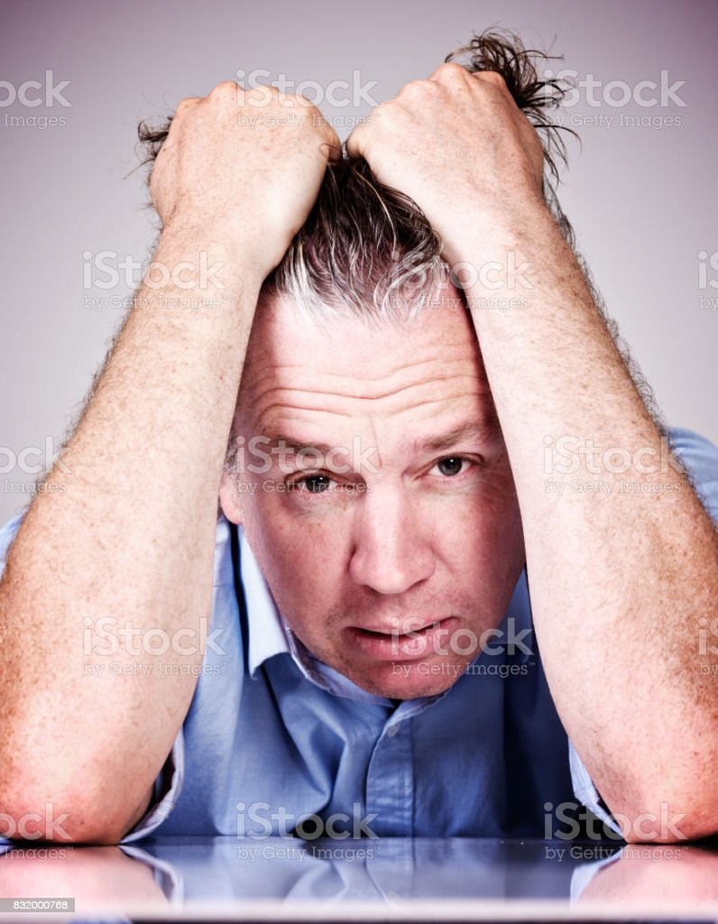 Worried mid-adult man tearing his hair out stock photo