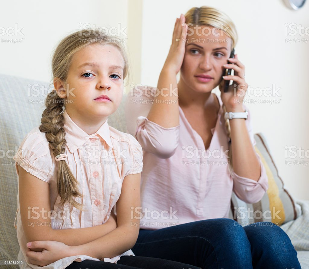 Worried mother calling doctor for daughter with abdominal pains stock photo