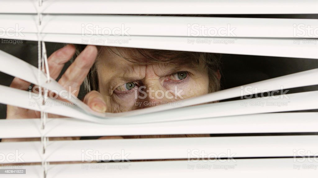 Worried old woman looks fearfully through blinds, frowning and suspicious stock photo