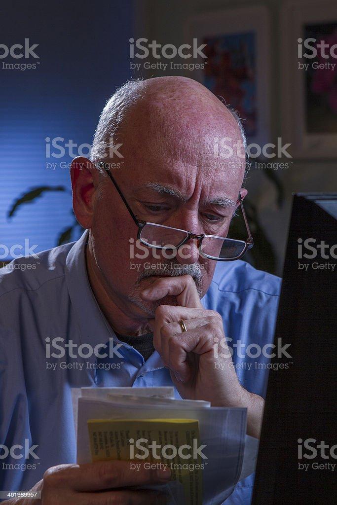 Worried older man looking at bills, vertical stock photo