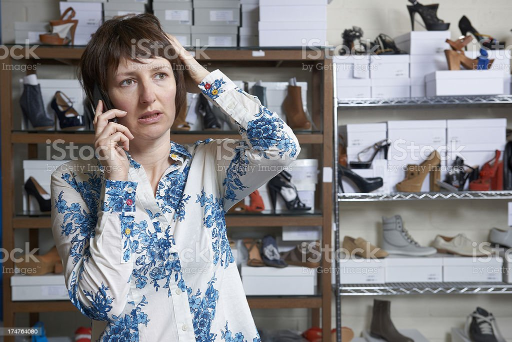 Worried Owner Of Shoe Store On Phone royalty-free stock photo