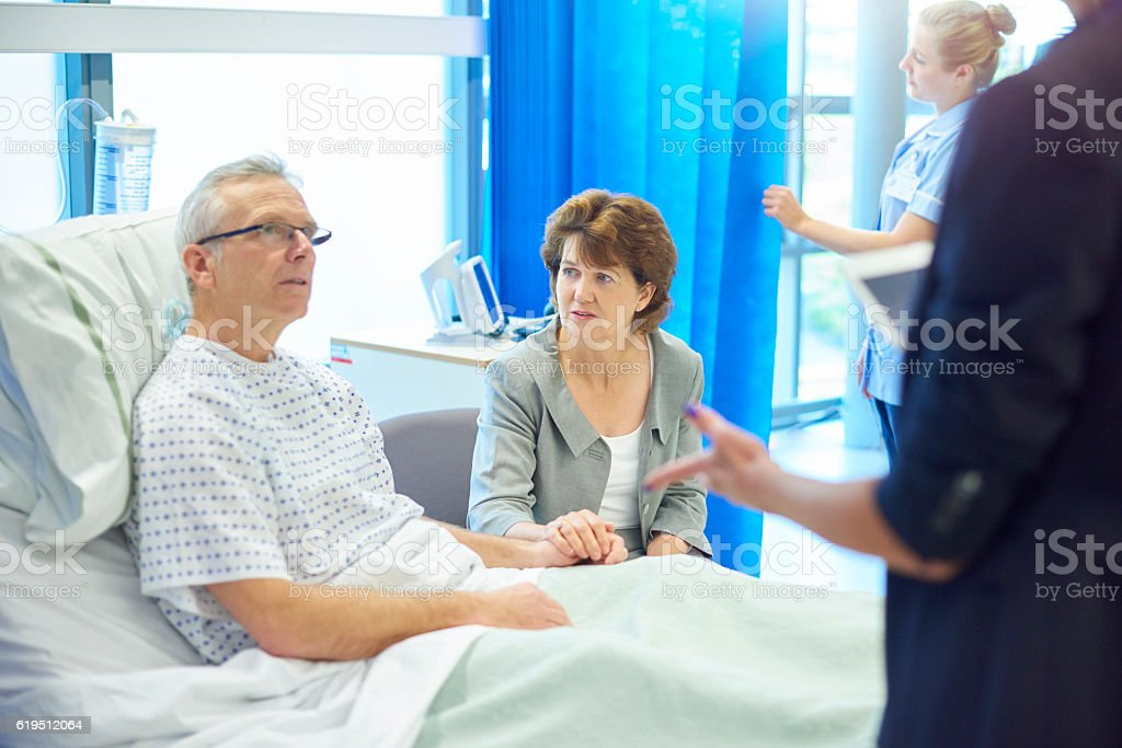 worried patient and wife chatting to doctor stock photo