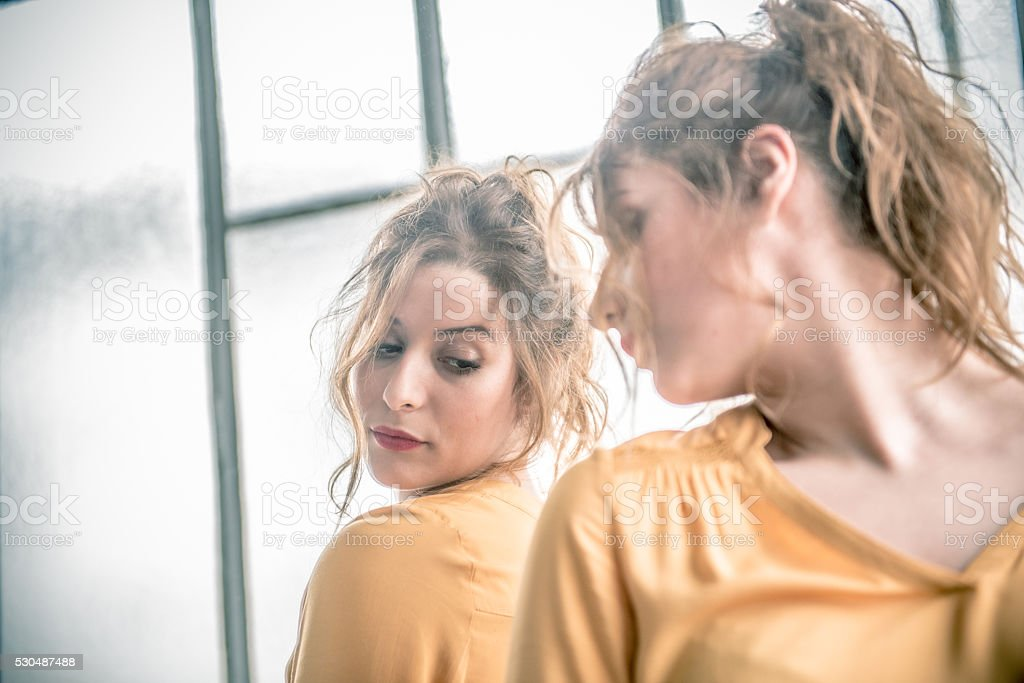 Worried Redhead Woman Looking at Herself in Mirror, Paris, France stock photo