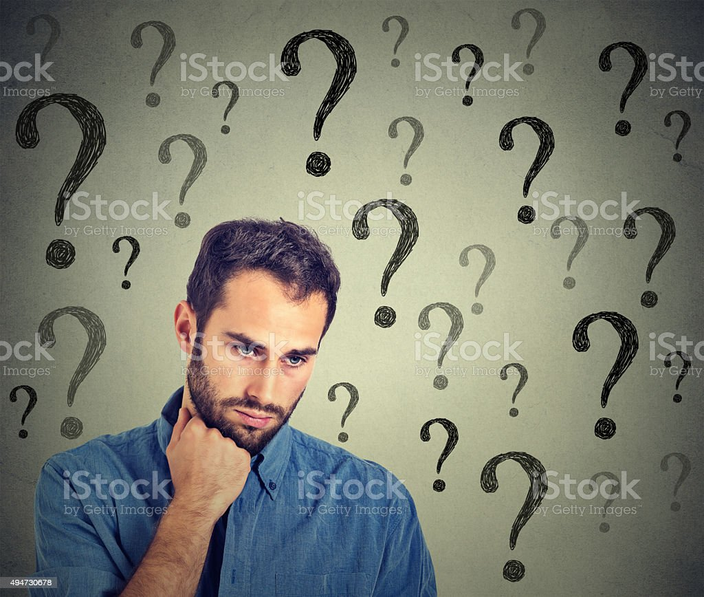 Worried sad man has many questions looking down stock photo