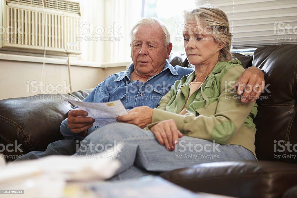 Worried Senior Couple Sitting On Sofa Looking At Bills stock photo