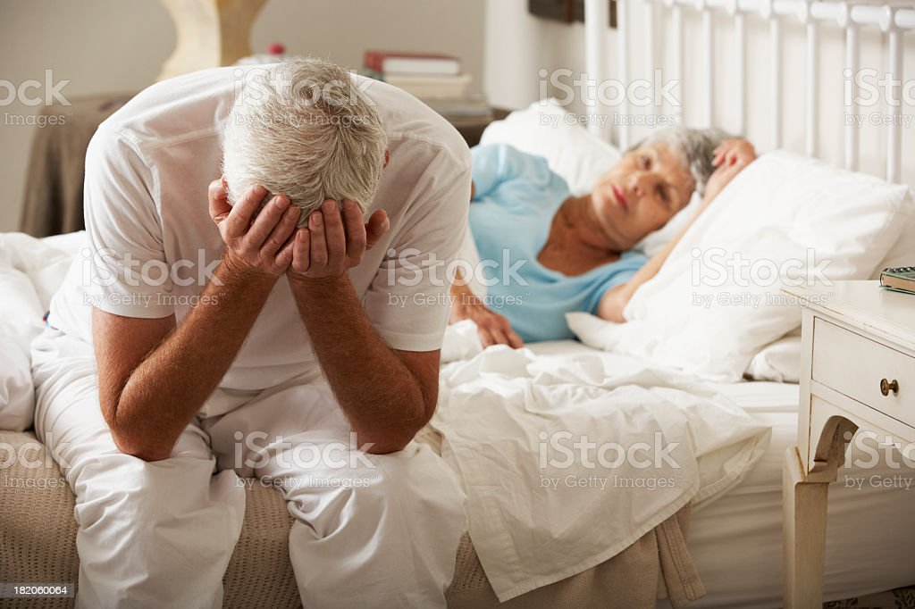 Worried Senior Man Sits On Bed Whilst Wife Sleeps stock photo