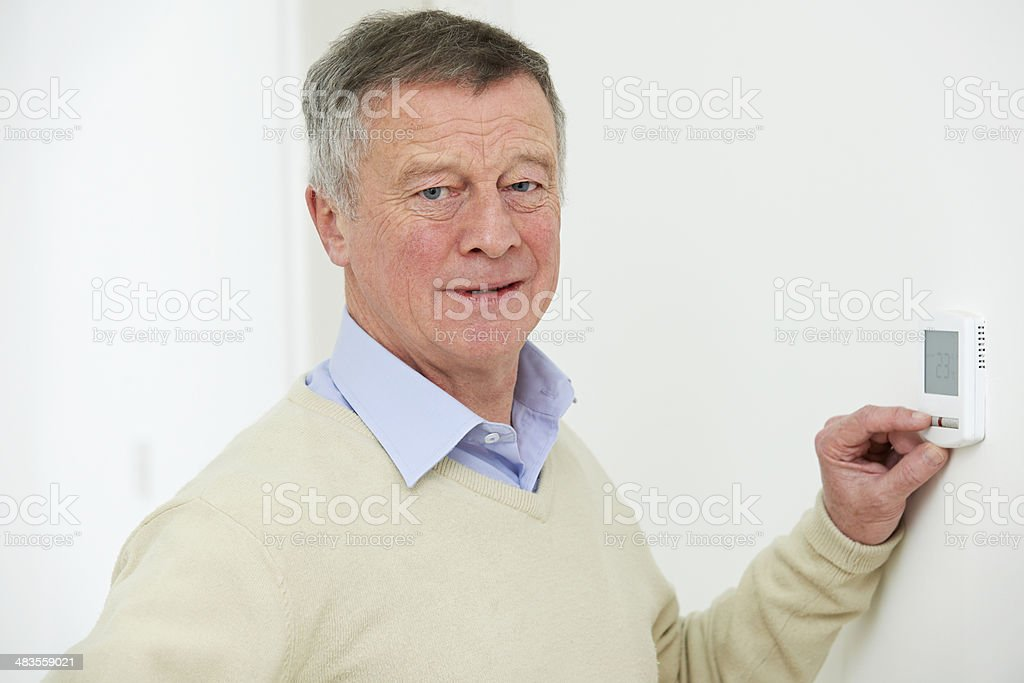 Worried Senior Man Turning Down Central Heating Thermostat royalty-free stock photo