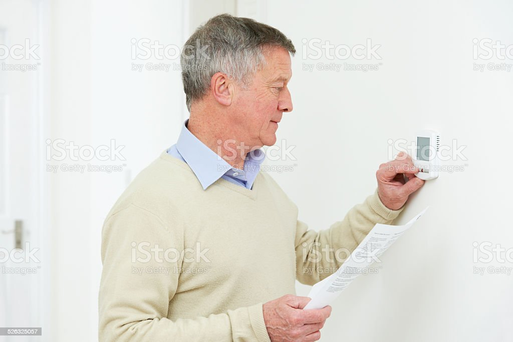 Worried Senior Man With Bill Turning Down Heating Thermostat stock photo