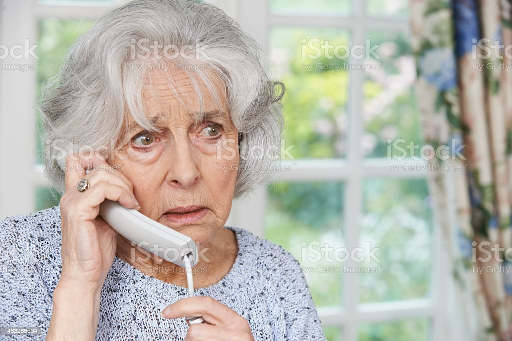 Worried Senior Woman Answering Telephone At Home stock photo