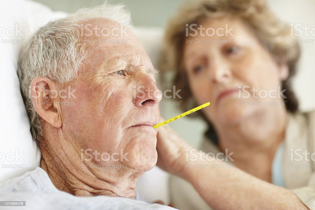 Worried senior woman comforting a sick elderly man stock photo