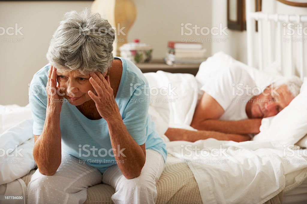 Worried Senior Woman Sits On Bed royalty-free stock photo