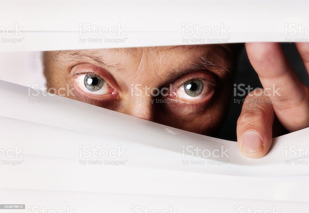 Worried watchful eyes peeping suspiciously through white Venetian blind stock photo
