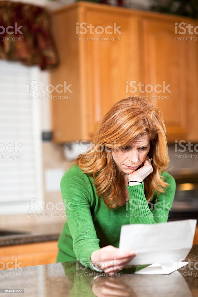 Worried woman going over bills stock photo