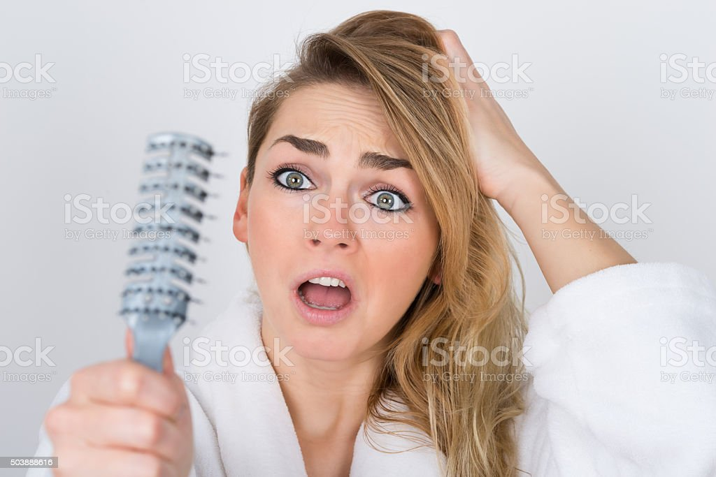 Worried Woman Looking At Comb stock photo