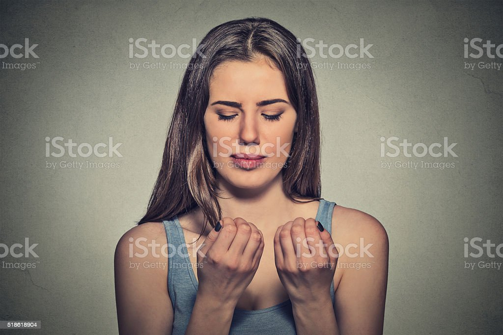 Worried woman looking at fingers nails obsessing about cleanliness stock photo