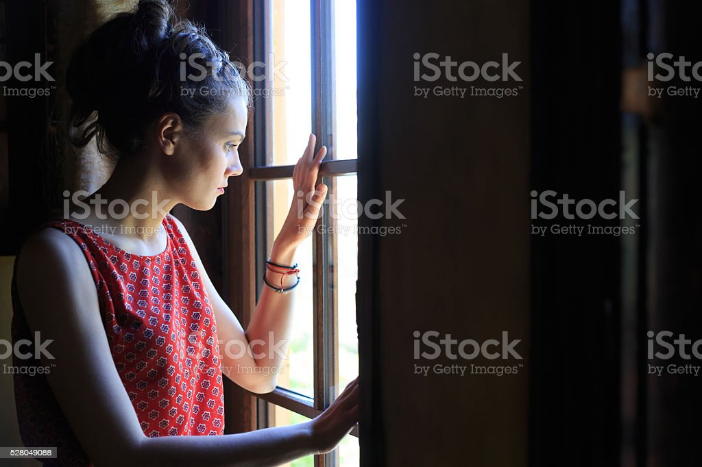 Worried woman looking through the window stock photo