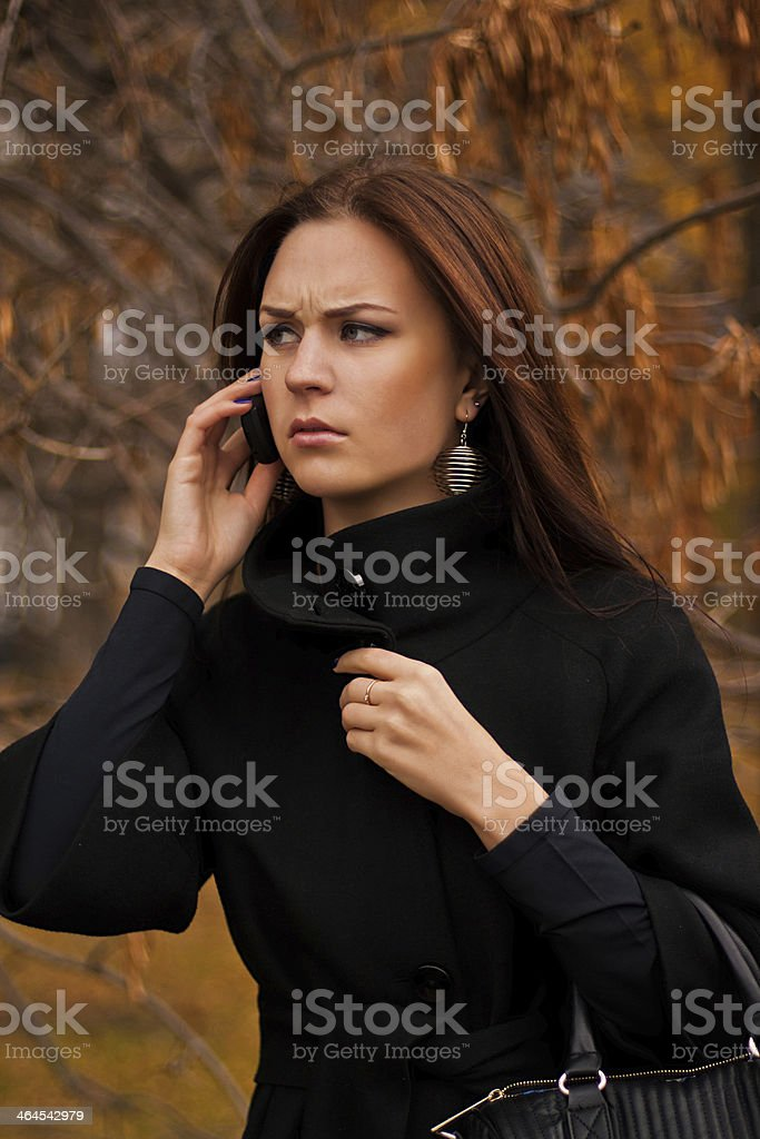 Worried woman on the phone outdoors stock photo