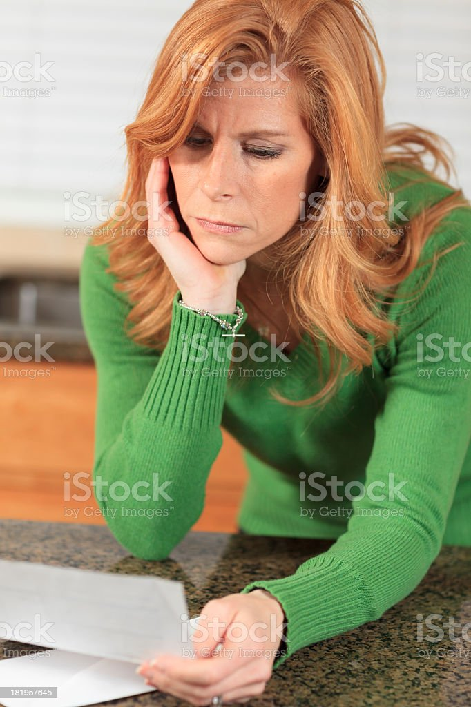 Worried woman reading bank statement stock photo