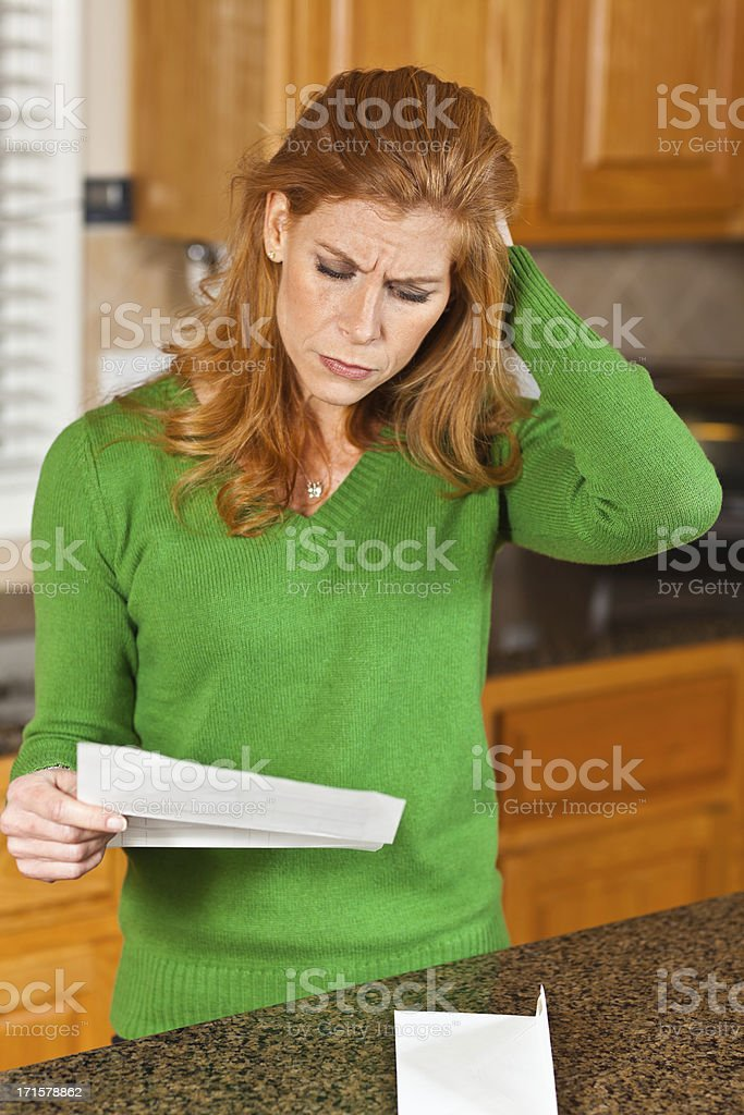 Worried woman reading letter stock photo