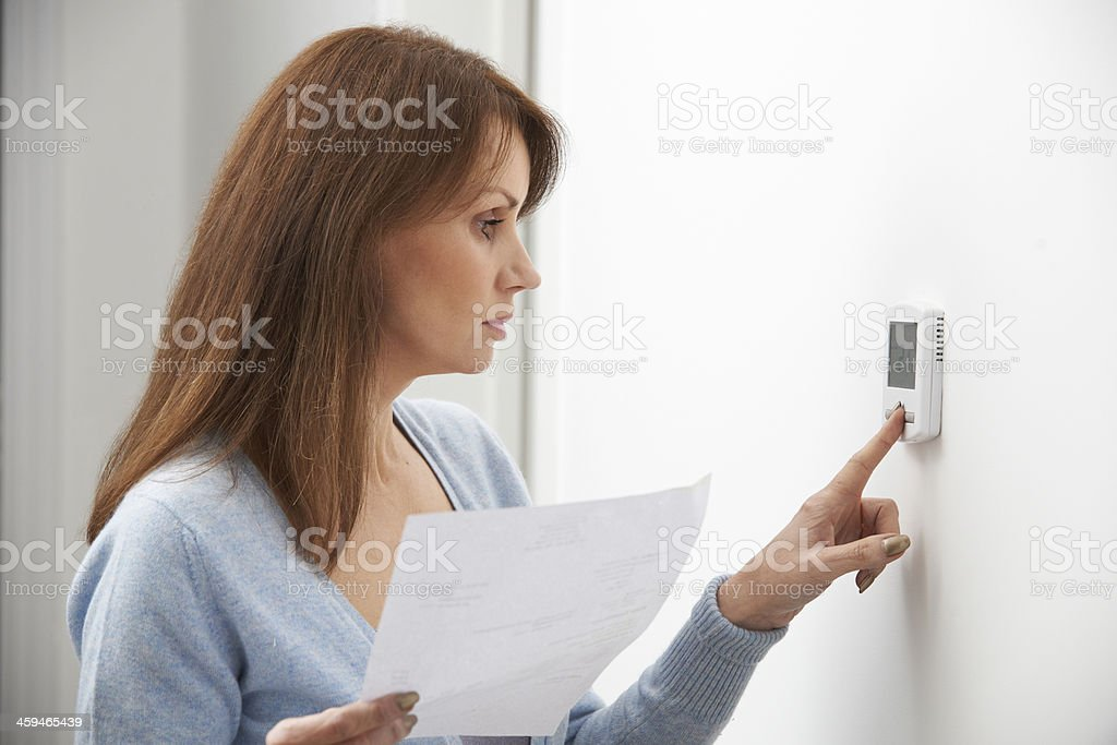 Worried Woman Turning Down Central Heating Thermostat stock photo