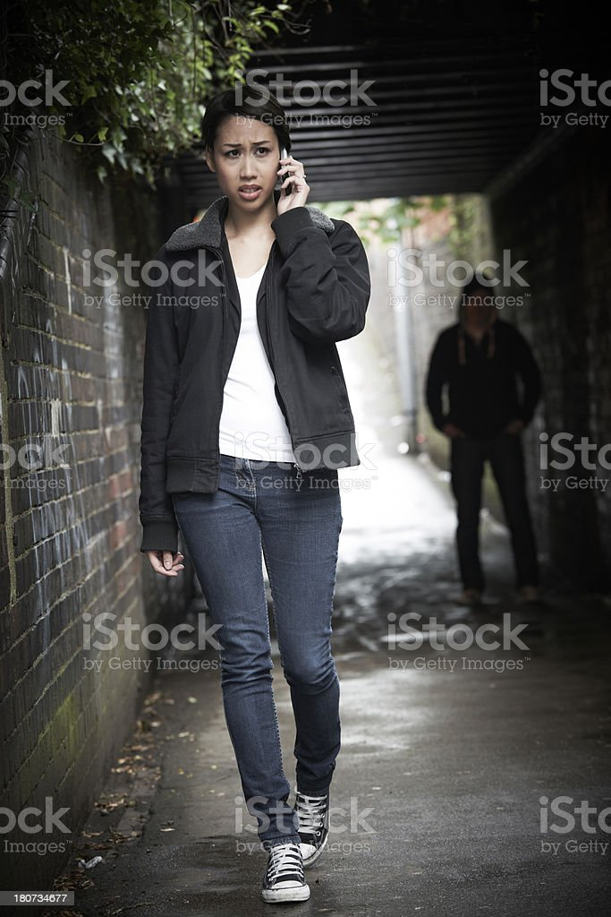 Worried Woman Walking Along Path With Sinister Figure Watching Her stock photo