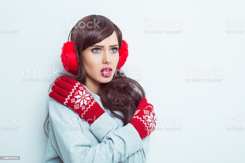 Worried woman wearing red earmuffs and gloves stock photo