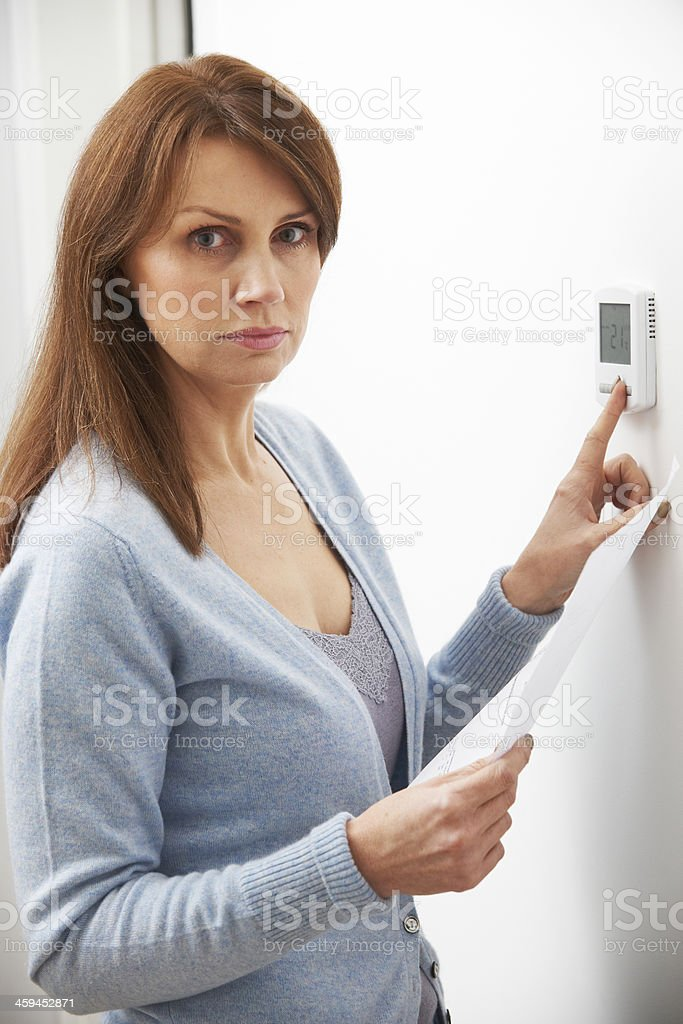Worried Woman With Heating Bill Turning Down Thermostat stock photo