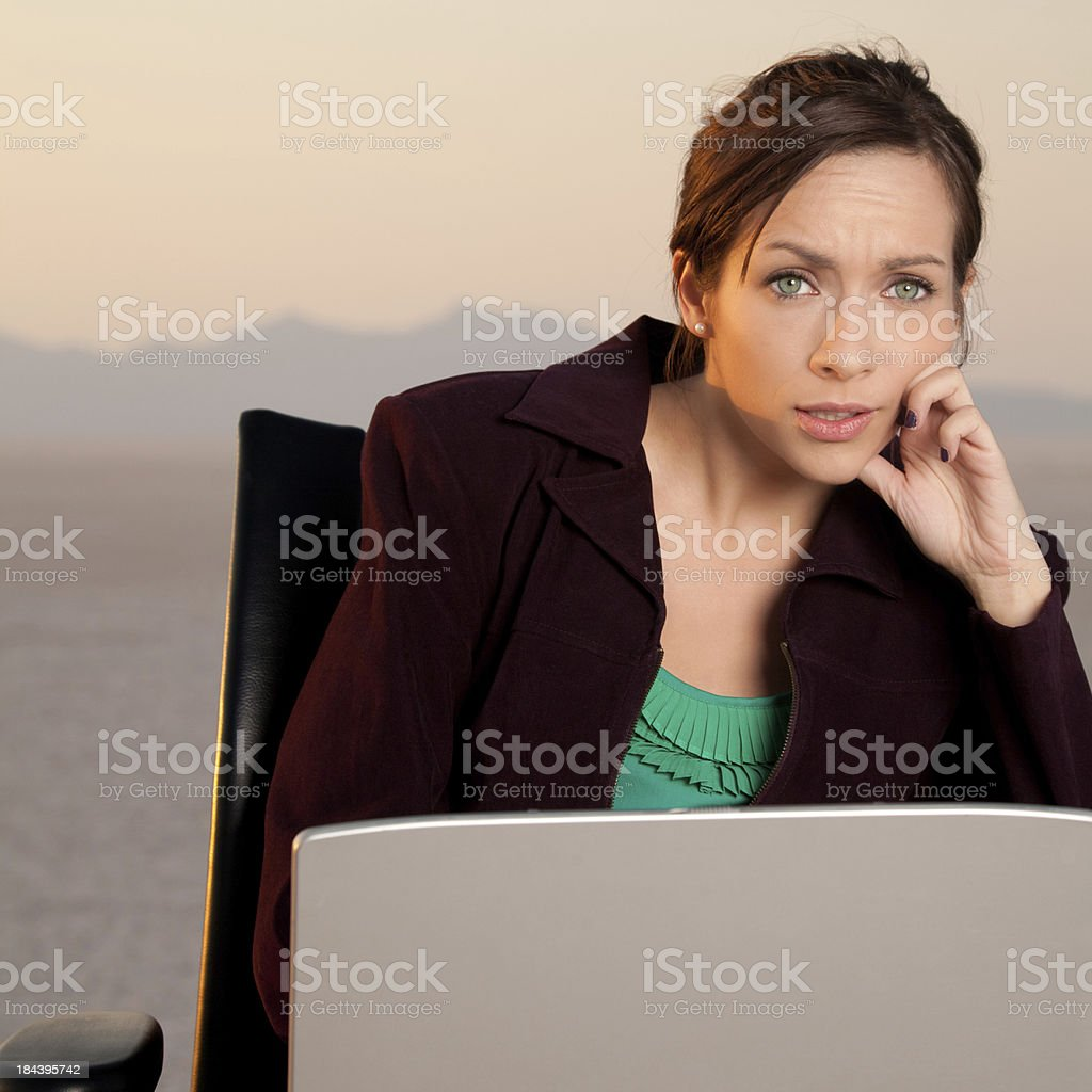 Worried young business woman sitting out in a desert royalty-free stock photo