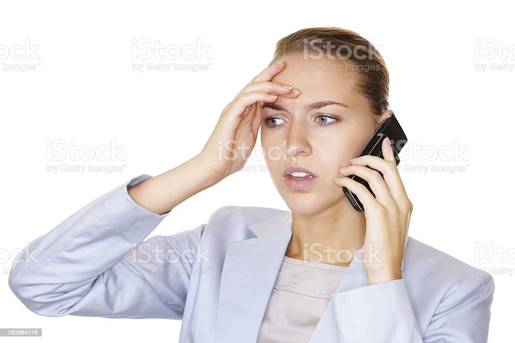 Worried young business woman speaking over cellphone on white royalty-free stock photo