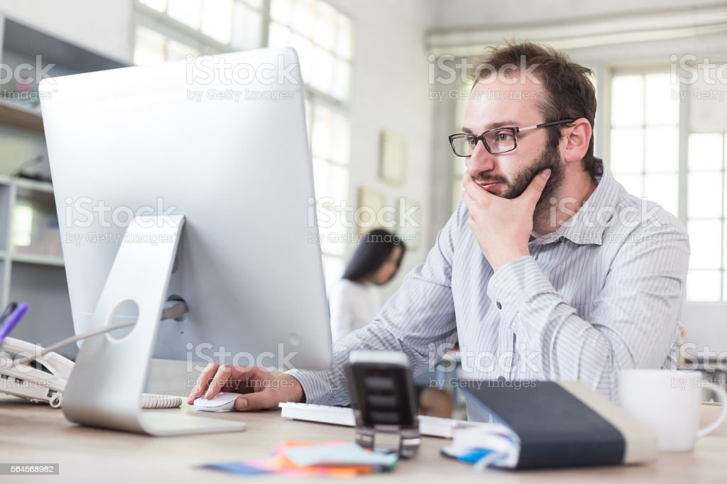 Worried young businessman with eyeglasses at workplace stock photo