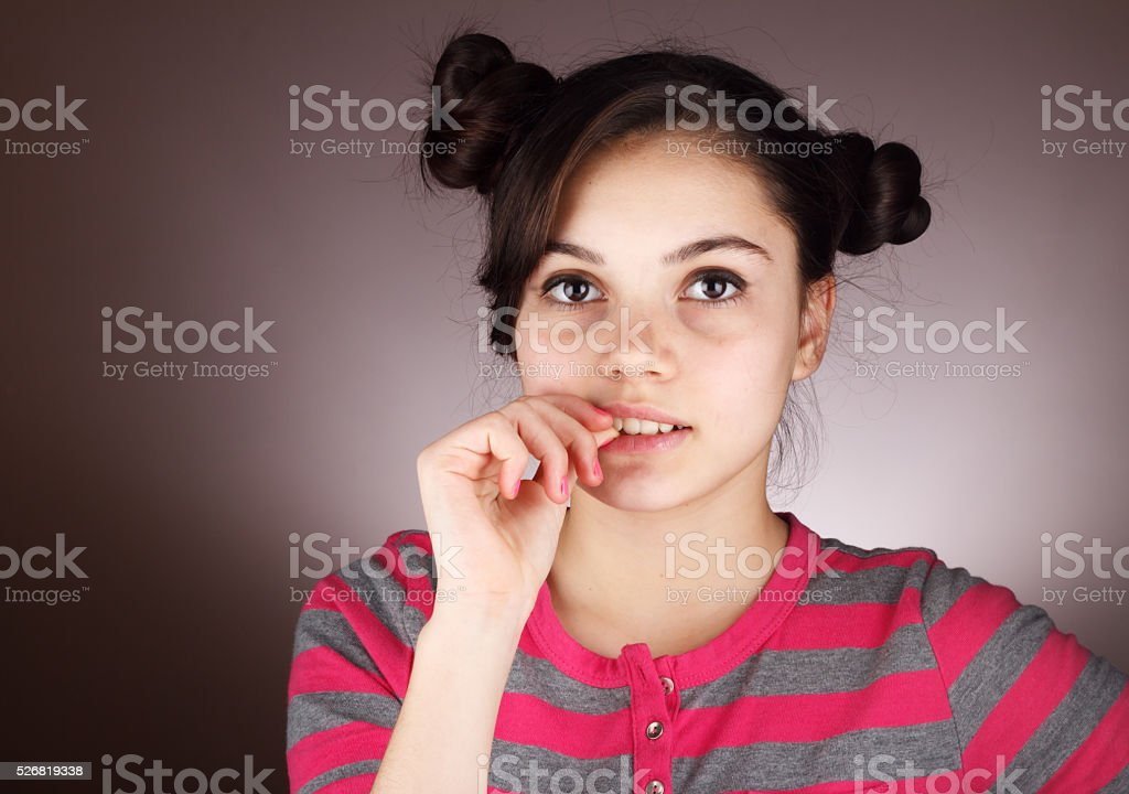 Worried young girl biting nail stock photo