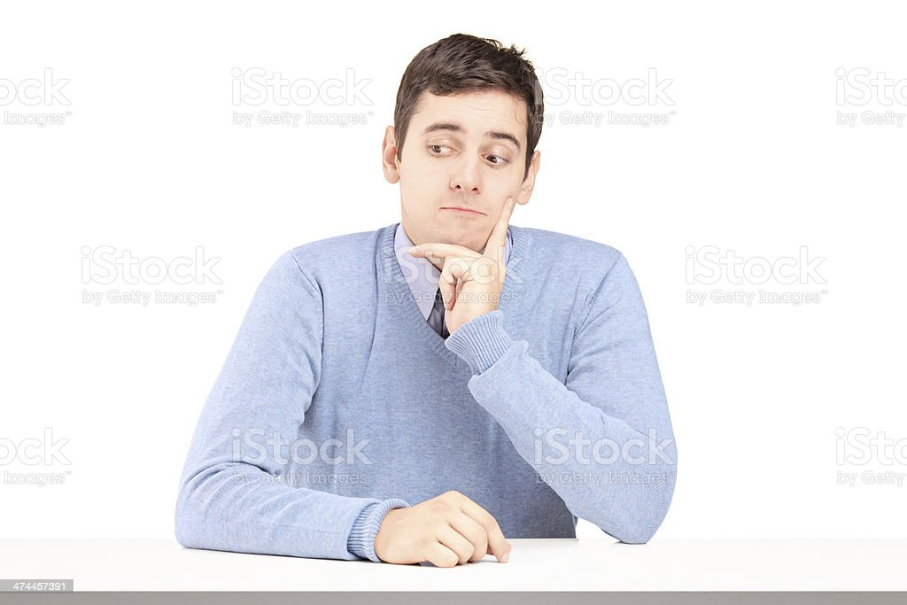Worried young man sitting at a desk royalty-free stock photo