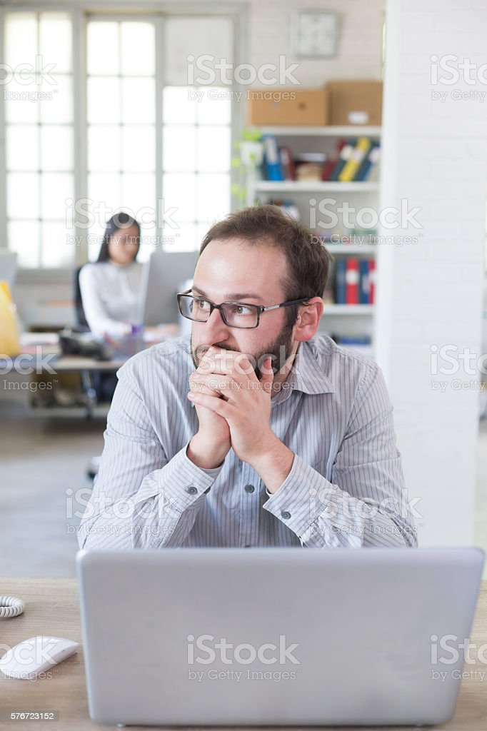 Worried young man with eyeglasses at workplace stock photo