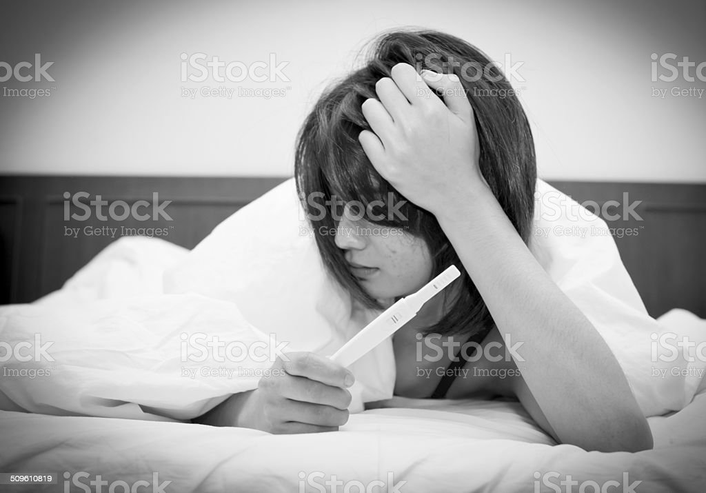 Worried Young Woman Checking Pregnancy Test,Black and White stock photo
