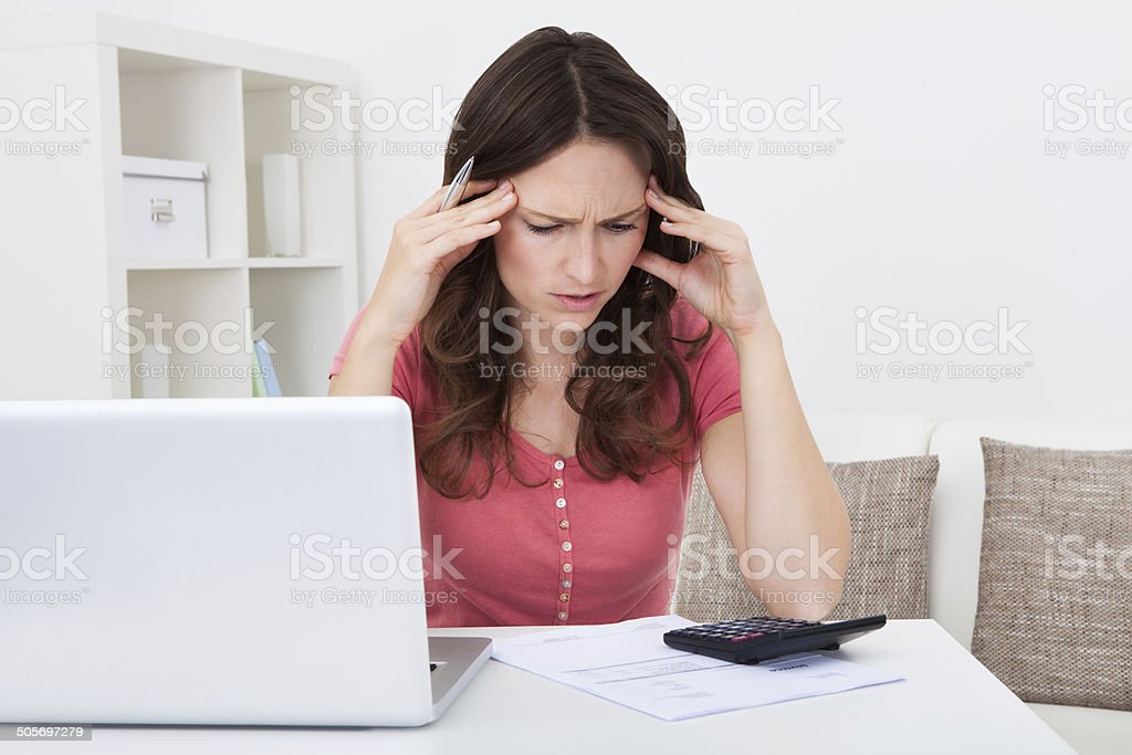 Worried Young Woman Doing Calculations stock photo
