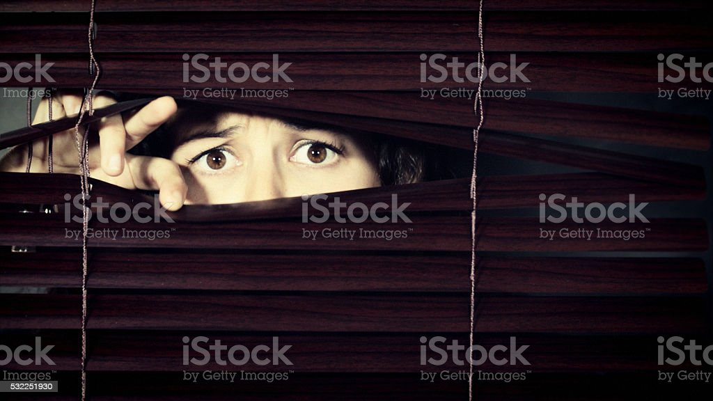 Worried young woman peeps through Venetian blind, frowning stock photo