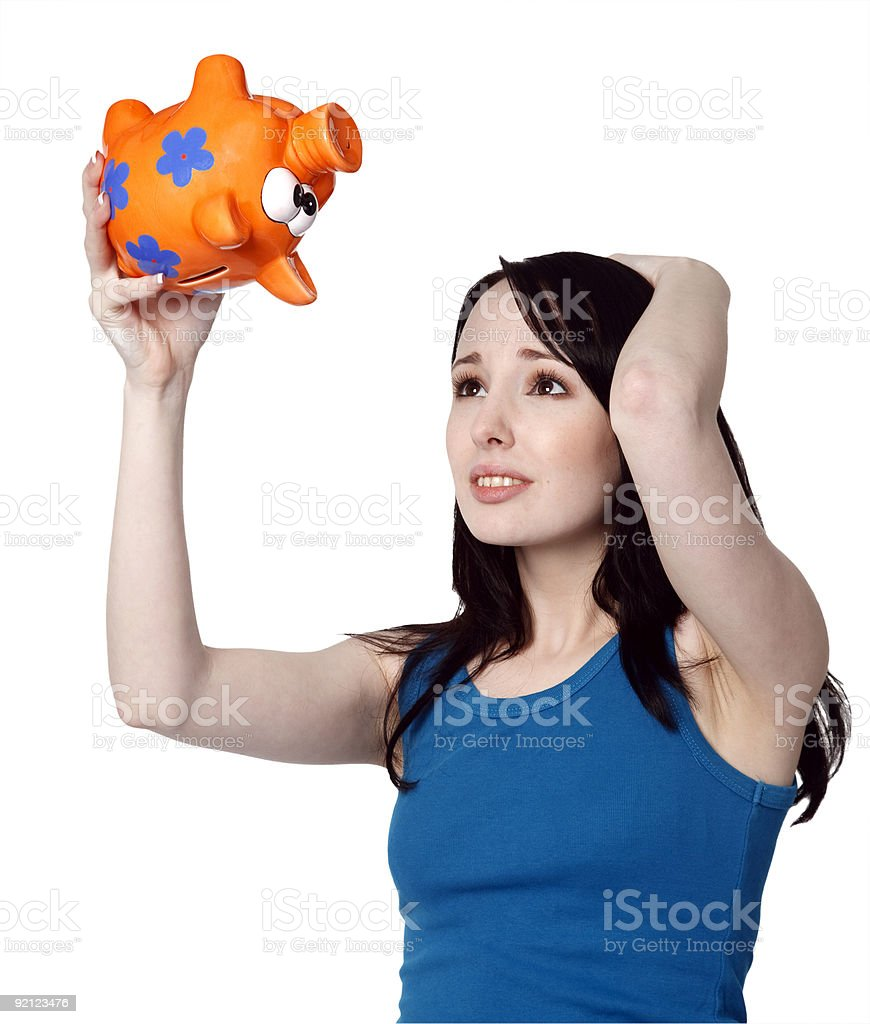 Worried young woman shaking an empty piggy bank royalty-free stock photo
