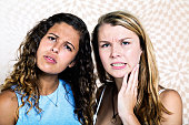 Worried young women reacting to something, intrigued but bothered