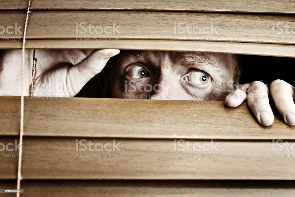 Worried-looking man peeps sideways through venetian blind stock photo