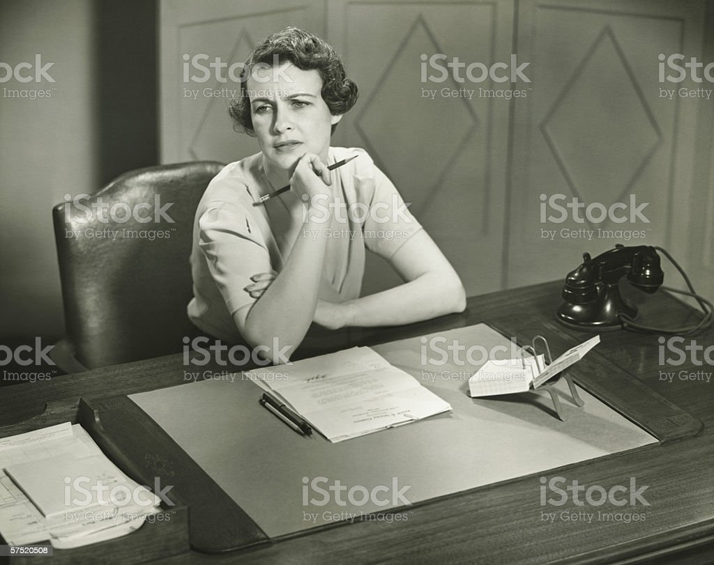 Worrying woman sitting at desk in office, (B&W) stock photo