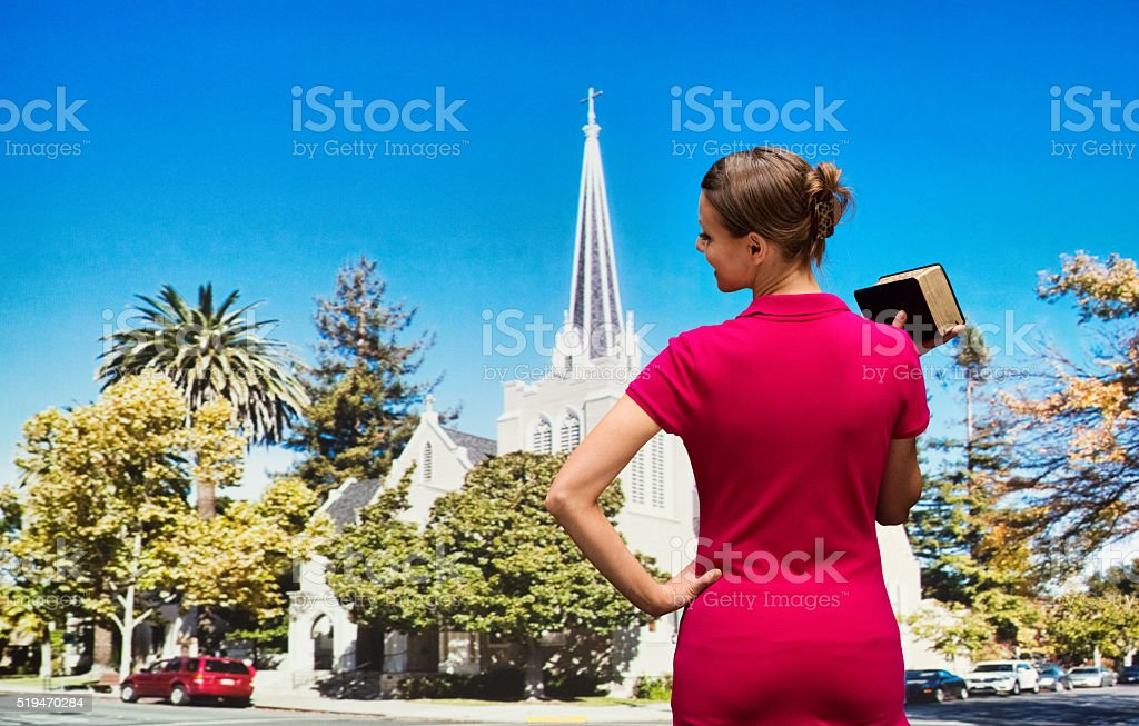 Worshipper attending church with bible in hand stock photo